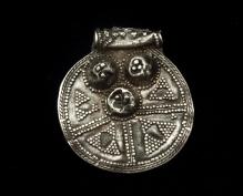 Zawieszka kolista wykonana ze srebra zdobiona pustymi guzkami, filigranem i ziarniną pochodząca ze skarbu ozdób srebrnych i monet znalezionego na wzgórzu należącym do majątku Kurowo (pow. koszaliński), koniec X w., 2,5 cm, fot. G. Solecki/A. Piętak